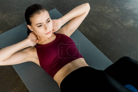 focused sportswoman doing abs exercise on fitness mat at gym