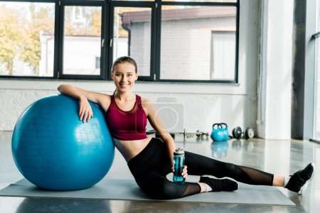 Photo for Beautiful fit sportswoman looking at camera and sitting on mat with blue fitness ball at sports center - Royalty Free Image