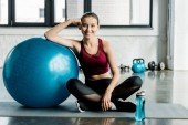 beautiful sportswoman looking at camera and sitting on mat with blue fitness ball at gym