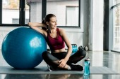 beautiful smiling sportswoman sitting on mat with blue fitness ball at gym