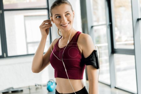 beautiful smiling sportswoman in smartphone armband putting on earphones at gym