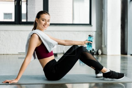 Photo for Smiling sportswoman with towel sitting on mat with sport bottle after working out at gym - Royalty Free Image