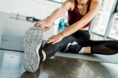 cropped view of sportswoman sitting on mat and doing stretching exercise at gym