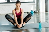 focused sportswoman sitting on mat and doing stretching exercise at sports center