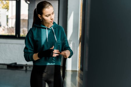 attractive sportswoman putting on sport gloves at gym