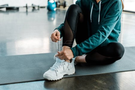Photo for Cropped view of sportswoman tying laces on training shoes while sitting on fitness mat at gym - Royalty Free Image