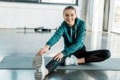 smiling sportswoman sitting on mat, looking at camera and doing stretching exercise at gym