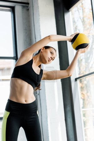 Photo for Focused beautiful sportswoman training and stretching with medicine ball at gym - Royalty Free Image