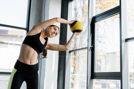 Photo pour Belle forme sportive de formation et d'étirements avec médecine-ball au gymnase - image libre de droit