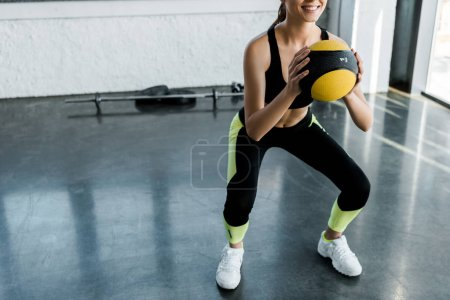 partial view of smiling sportswoman doing squats with medicine ball at gym