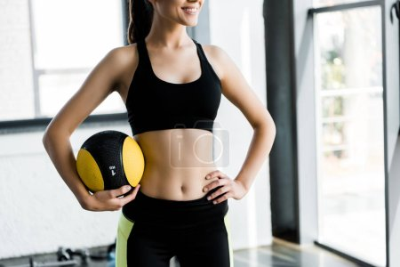 cropped view of  beautiful smiling sportswoman holding medicine ball at gym