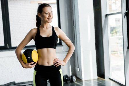 Photo pour Belle sportive tenant le ballon de médecine à la salle de gym - image libre de droit