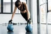 sportive forte dans les gants d'haltérophilie faire exercice planche sur kettlebells au gymnase
