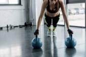determined sportswoman in weightlifting gloves doing plank exercise on kettlebells at sports center