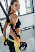 attractive smiling sportswoman looking at camera while training with resistance bands at fitness studio