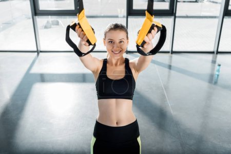 attractive sportswoman looking at camera and training with resistance bands at fitness studio