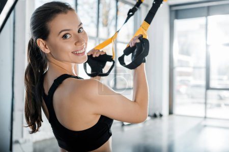 Photo for Beautiful smiling sportswoman looking at camera and training with resistance bands at gym - Royalty Free Image