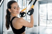 beautiful smiling sportswoman looking at camera and training with resistance bands at gym
