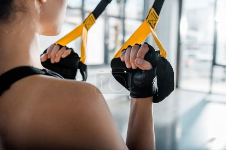 Photo for Cropped view of sportswoman training with resistance bands at gym - Royalty Free Image
