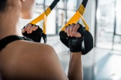 cropped view of sportswoman training with resistance bands at gym