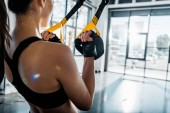 cropped view of athletic sportswoman training with resistance bands at gym
