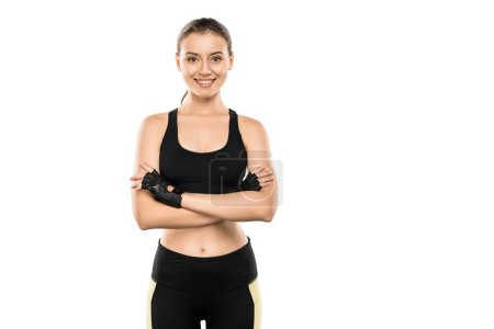 smiling sportswoman in weightlifting gloves with arms crossed looking at camera isolated on white