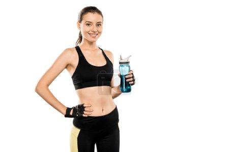 Photo pour Sportive souriante tenant une bouteille de sport et regardant la caméra isolée sur blanc - image libre de droit