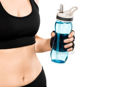 partial view of sportswoman holding sport bottle isolated on white