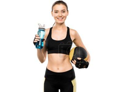 Foto de Atractivo deportista sosteniendo la botella del deporte y la bola de medicina aislada en blanco - Imagen libre de derechos