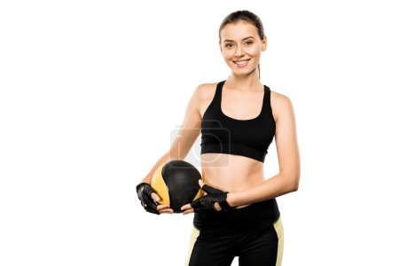 Photo for Smiling sportswoman looking at camera and holding medicine ball isolated on white - Royalty Free Image