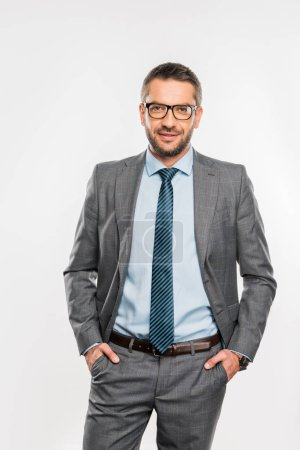 handsome businessman in suit and eyeglasses standing with hands in pockets and smiling at camera isolated on white