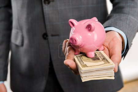 Foto de Primer plano vista parcial del empresario con billetes de dólar y hucha - Imagen libre de derechos