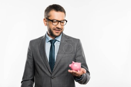 handsome businessman in suit and eyeglasses holding piggy bank isolated on white