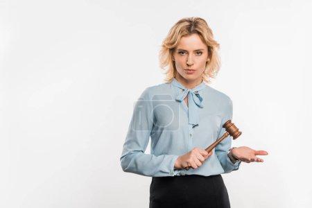 Photo pour Juge féminine grave tenant marteau en bois et regardant la caméra isolée sur blanc - image libre de droit
