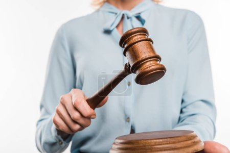 cropped shot of female judge holding wooden hammer isolated on white