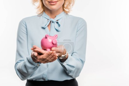cropped shot of smiling businesswoman holding pink piggy bank isolated on white