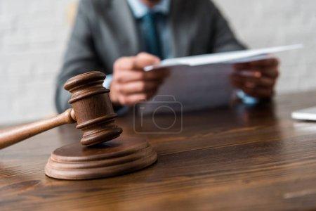 Photo pour Vue rapprochée du marteau en bois et du juge travaillant avec des documents derrière - image libre de droit