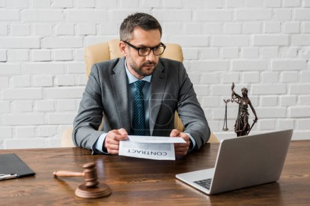 serious male lawyer holding contract and looking at laptop in office