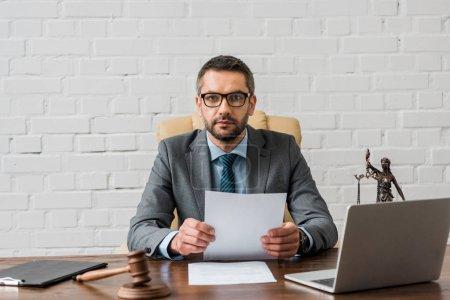 Photo pour Avocat sérieux dans les lunettes de travail avec des papiers et en regardant la caméra dans le bureau - image libre de droit