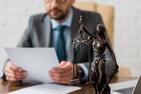 Photo for Close-up view of lady justice statue and lawyer working working with papers behind - Royalty Free Image