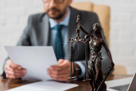 Photo pour Vue rapprochée de Dame justice statue et juriste travaillant avec papiers derrière - image libre de droit