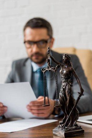 Photo pour Vue rapprochée de Dame justice statue et mâle avocat travaillant derrière - image libre de droit