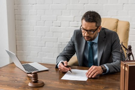 high angle view of concentrated male lawyer in eyeglasses working with document in office