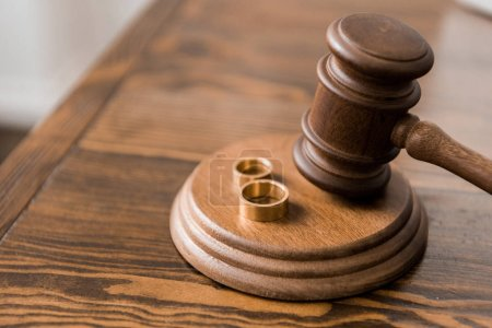 close-up view of judge hammer and wedding rings on wooden table, divorce concept