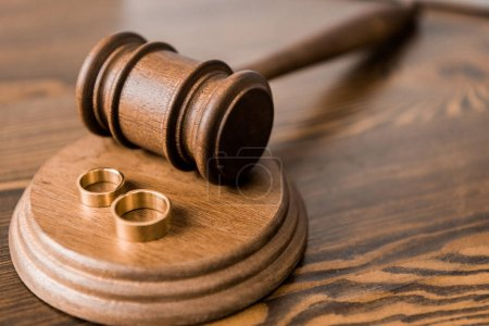 close-up view of wooden hammer and wedding rings on table, divorce concept