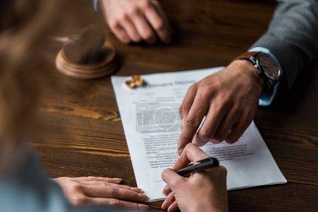 Photo pour Vue partielle du juge pointant du doigt les papiers et le client signant le jugement de divorce - image libre de droit