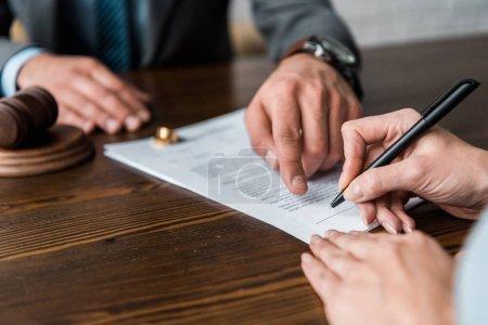 Photo pour Recadrée tir du juge pointant à papiers et signature de divorce - image libre de droit