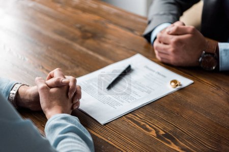 partial view of hands of lawyer and client, divorce decree and wedding rings on table