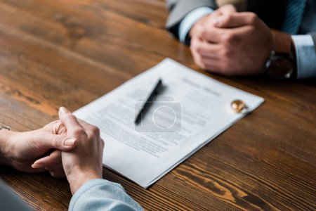 partial view of lawyer and client sitting at table with divorce decree and wedding rings