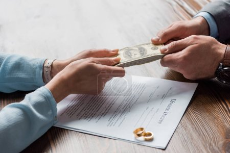 cropped shot of lawyer and client holding dollar banknotes above divorce decree with wedding rings